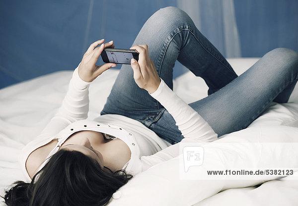 Teenager Mädchen mit Handy im Bett