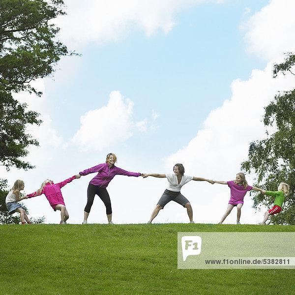 Girls playing tug-of-war in field