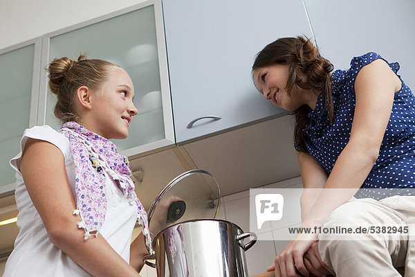 Smiling girls cooking in kitchen