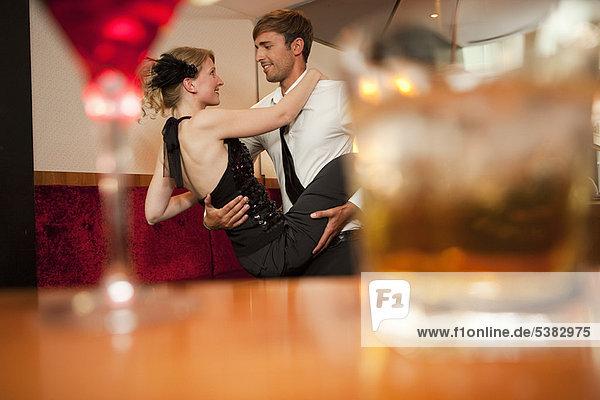 Lächelndes Paar tanzt in der Bar