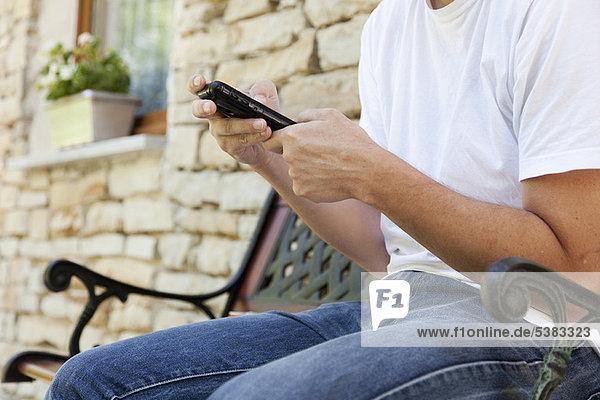Mann mit Handy auf der Bank