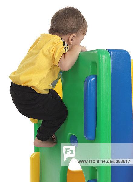 Junge  anderthalb Jahre  klettert auf einer Rutsche