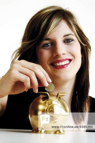 Junge Frau wirft Geld in ein goldenes Sparschwein