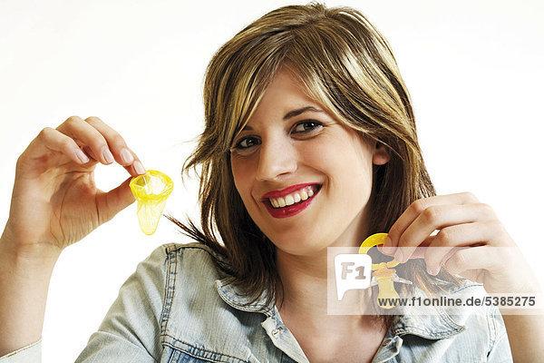 Junge Frau hält einen Schnuller und ein Kondom in der Hand - Symbol Kind oder Karriere