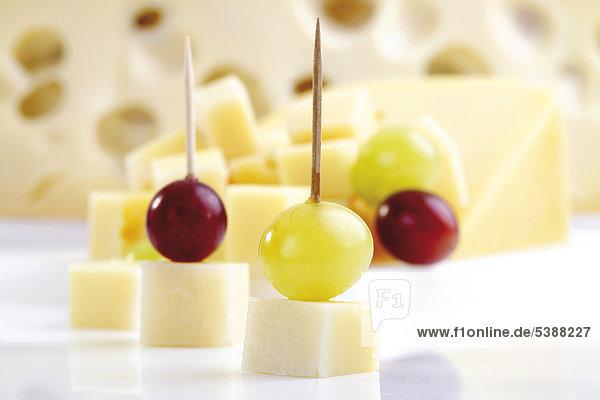 Käsewürfel und Käsepicker mit Trauben  dahinter ein halbes Käserad
