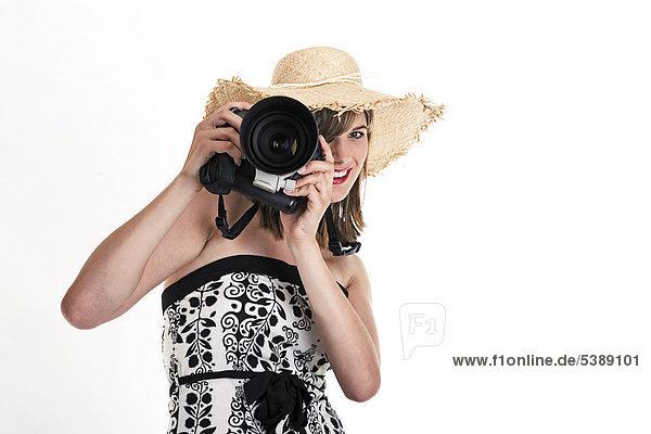 Junge Frau mit Sonnenhut und Digitalkamera