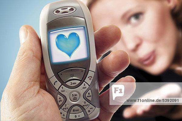 Handy mit blauem Herz  im Hintergrund junge Frau - Symbol für Liebesgruß