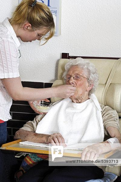 Im Pflegeheim  Altenheim  Pflegerin reicht einer Seniorin Essen an