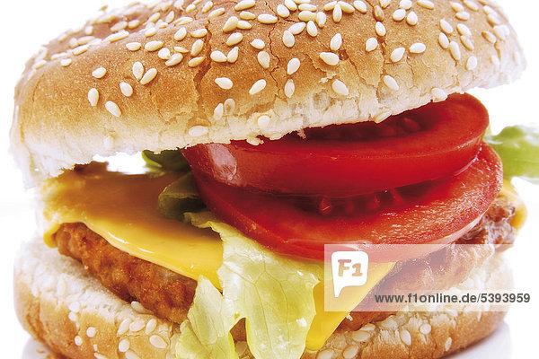 Cheeseburger mit Tomate und Salat auf Sesambrötchen