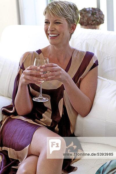 Reife Frau in Kaftan entspannen und Wein trinken