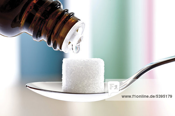 Homöopathische Tropfen  Würfelzucker auf Löffel