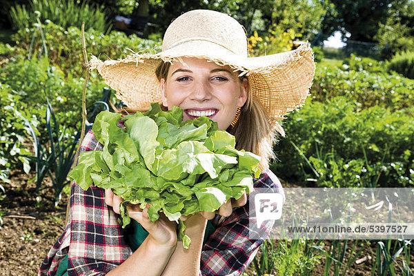 Junge Gärtnerin mit Kopfsalat