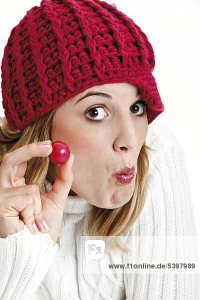 Young woman in a white turtleneck sweater with red woolen hat and chewing gum ball