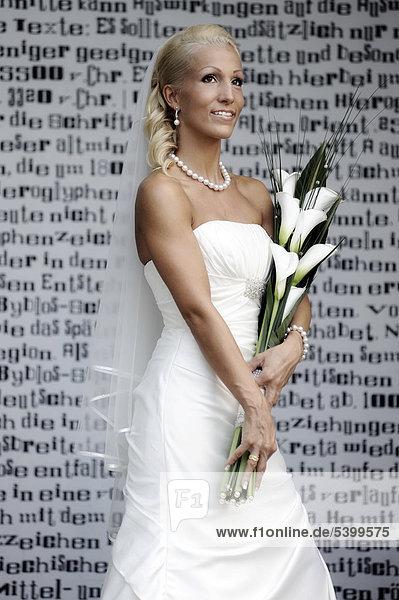 Hochzeit  lächelnde Braut mit Brautstrauß steht vor einer Wand mit Schriftzeichen