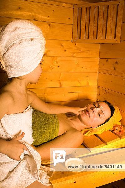 Junge Frau und ein Mädchen in der Sauna