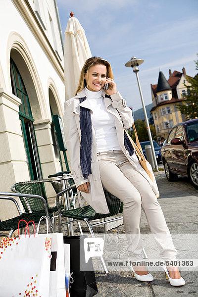 Junge Frau telefoniert beim Einkaufen in der Stadt  Sonneberg  Thüringen  Deutschland  Europa