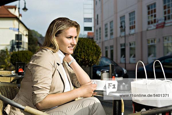 Junge Frau sitzt in einem StraßencafÈ  Sonneberg  Thüringen  Deutschland  Europa