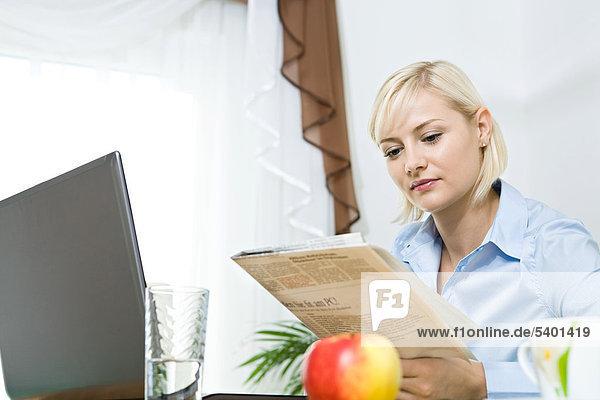 Eine junge Frau liest Zeitung im Wohnzimmer