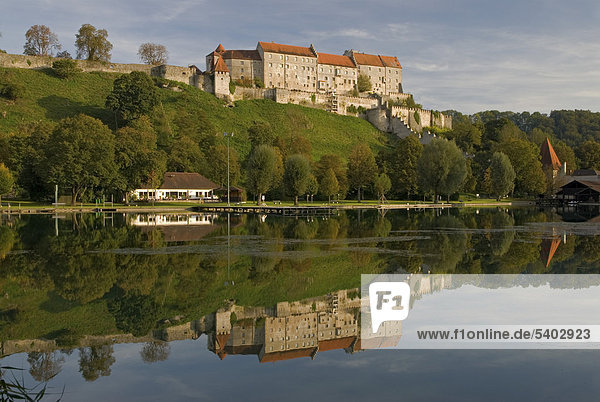 Die Burg zu Burghausen spiegelt sich im ruhigen Woehrsee  Oberbayern  Deutschland  Europa