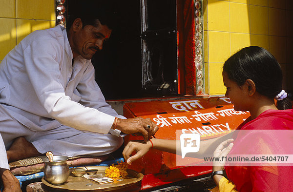 Priest exchanging blessings with donations at Har Ki Pauri Ghat in Haridwar  Uttarakhand  formerly Uttaranchal  India  Asia