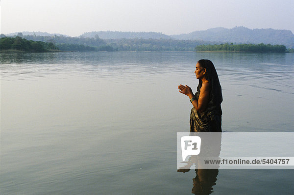 Eine Frau steht im kalten klaren Wasser des Flusses Ganges und betet zu Gott  Haridwar  Uttarakhand  früher Uttaranchal  Indien  Asien