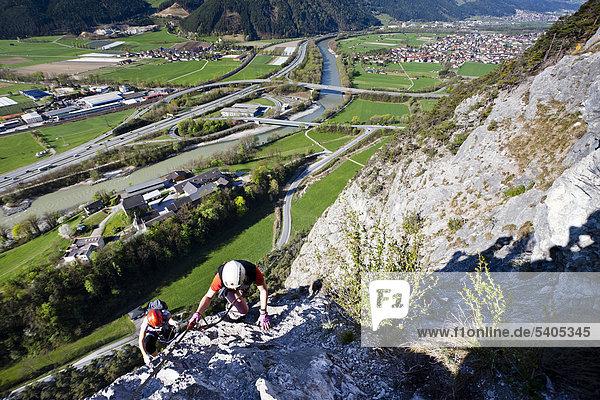 Kletterer beim Aufstieg über den Kaiser-Max-Klettersteig bei der Martinswand neben Innsbruck  hinten das Inntal und Zirl  Nordtirol  Tirol  Österreich  Europa