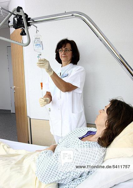 Krankenschwester legt einer Patientin im Krankenbett einen Tropf  Infusionslösung  an  Krankenhaus
