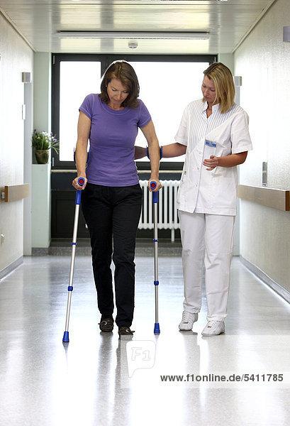 Krankenschwester hilft Patientin bei Gehversuchen an Gehhilfen  Mobilisierung nach einer Operation  Krankenhaus