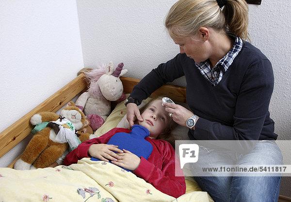 Mädchen  10 Jahre  liegt krank im Bett  mit Grippe  Erkältung  Schnupfen  Mutter misst Fieber mit einem digitalen Hautthermometer