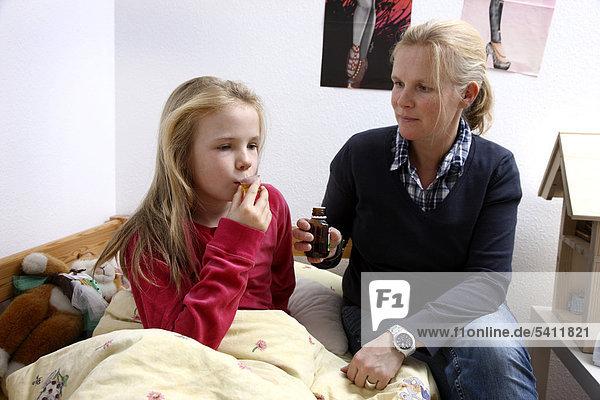 Mädchen  10 Jahre  mit Grippe  Erkältung  Schnupfen  Fieber  Husten  bekommt von der Mutter Hustensaft verabreicht