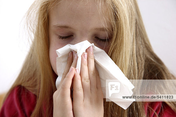 Girl  10 years old  with a cold  flu  fever  blowing her nose