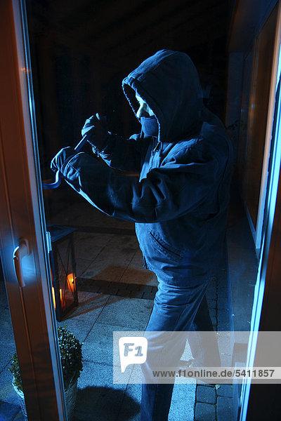 Einbrecher bricht mit einem Brecheisen die Verandatür auf  Symbolbild Wohnungseinbruch  Einbruch