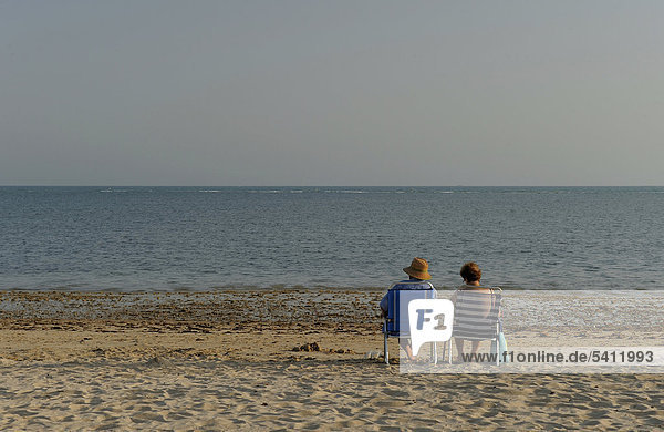 Paar sitzt am Strand  Rota  Andalusien  Spanien  Europa