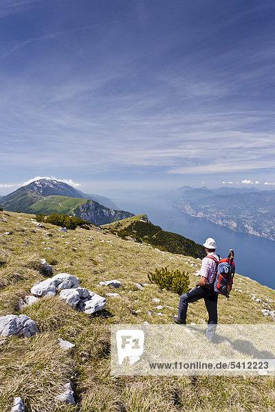 Hiker on Mt Monte Altissimo  above Nago-Torbole  Lake Garda below  Mt Monte Baldo in the back  Trentino  Italy  Europe