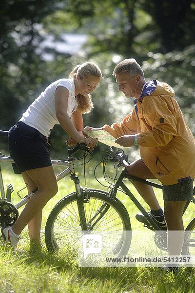 Paar liest Karte bei Ausflug mit Fahrrädern  Frau 42 Jahre  Mann 52 Jahre