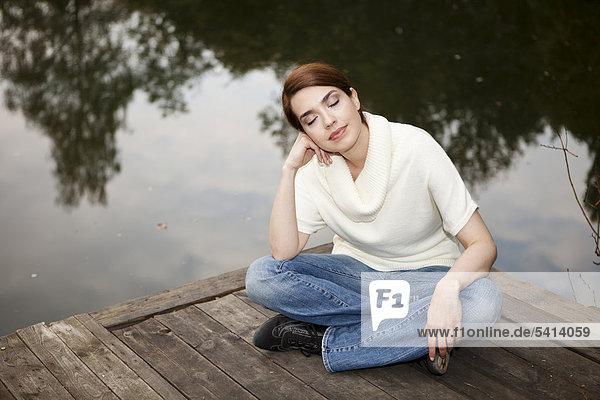 Junge Frau sitzt mit geschlossenen Augen auf einem Steg am See