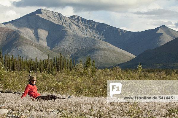 Junge Frau entspannt  genießt  sitzt inmitten von Wollgras im Abendlicht  Wind River  Yukon Territory  Kanada