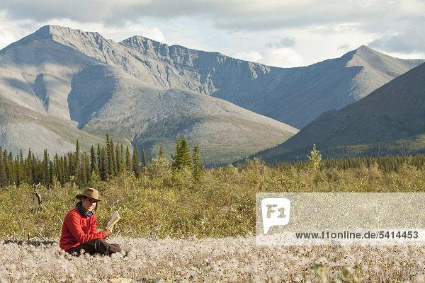 Junge Frau liest ein Buch  entspannt  sitzt im Wollgras  Peel Watershed  hinten die nördlichen Mackenzie Mountains  Yukon Territory  Kanada