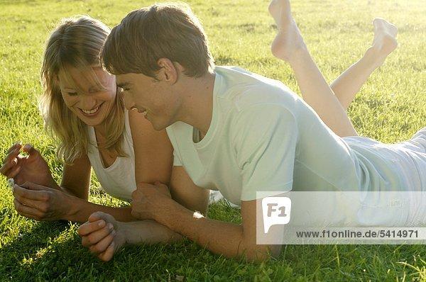 Junges Paar liegt auf einer Wiese