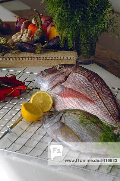 Zwei Fische mit Zitronen und Gemüse