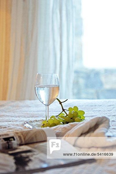 Trinken Glas  Trauben und Magazine auf Bett