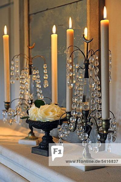 Brennende Kerzen und Blüten auf Kante