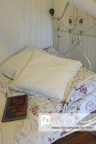 Kissen und Buch auf Bett