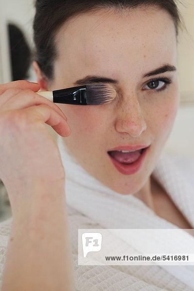 Junge Frau im Bad mit Make-up Pinsel