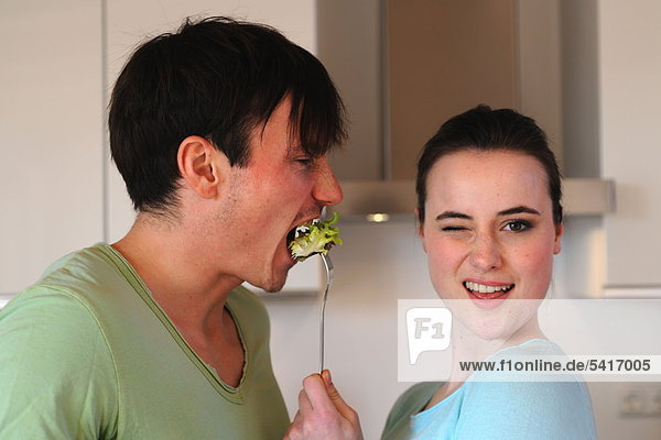 Young woman feeding man with salad