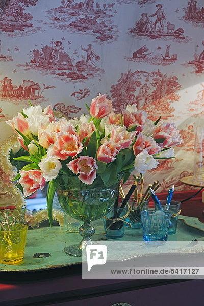 Reihe von Blumen und Gläser auf Kommode