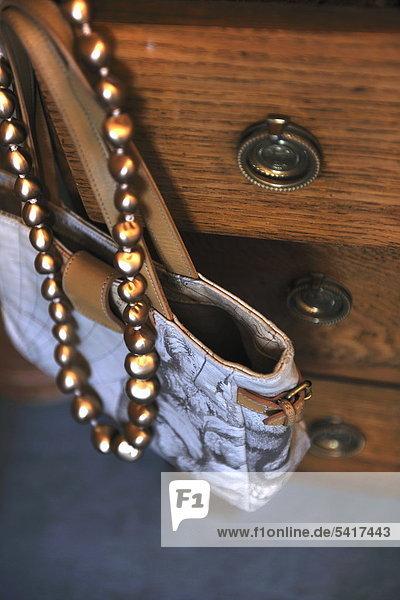 Handtasche und Halskette hanging in Kommode
