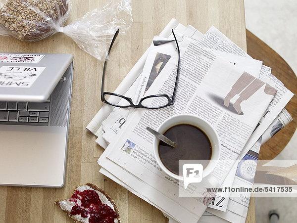 Frühstückstisch Zeitung mit laptop