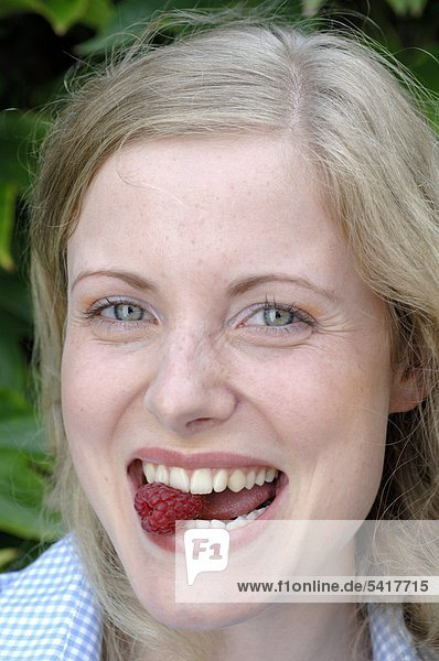 Happy young Woman Essen Himbeeren
