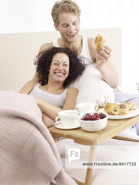 Happy couple having breakfast in bed